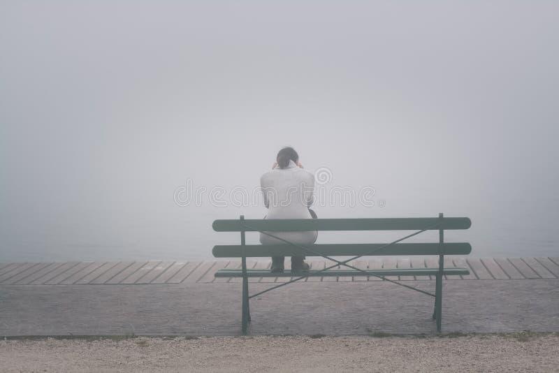 Anonyme Frau, die allein auf einer Bank sitzt stockbilder
