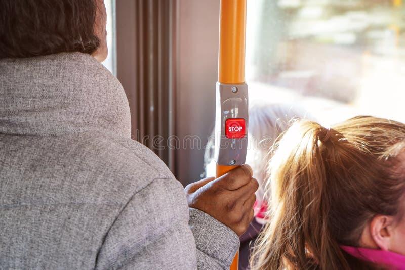 Anonyme Frau, die auf Bus der öffentlichen Transportmittel, Detail zu ihrer Hand hält gelbe Stange unter STOPP-Taste, Sonne hinte stockfoto