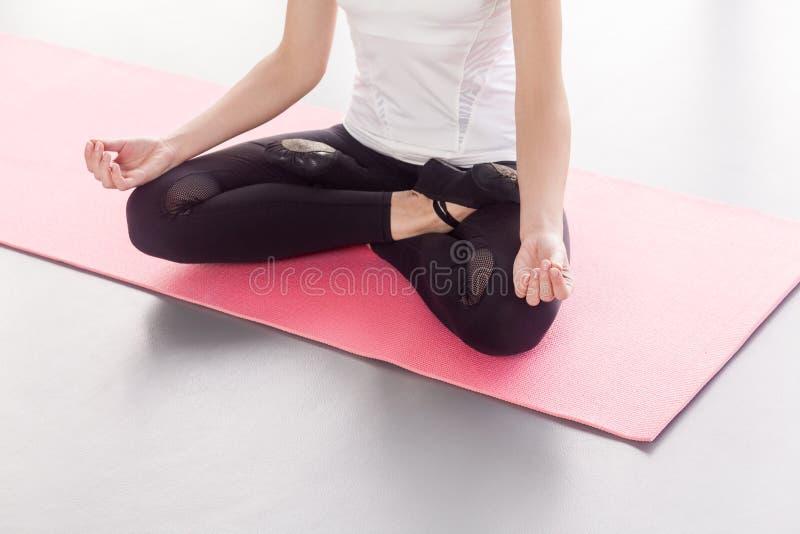Anonyme Frau, die in der Lotoslage, Yoga tuend sitzt lizenzfreies stockfoto