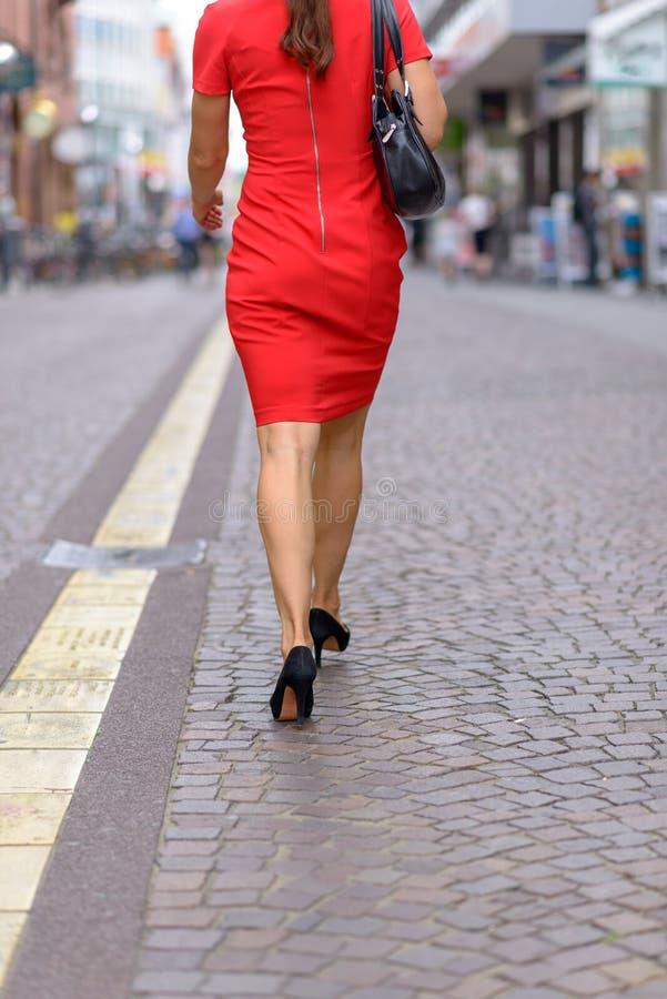Anonyme Frau, die mitten in einer Straße geht lizenzfreies stockbild