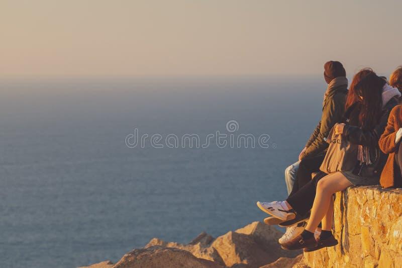 Anonyme Leutestellung am Rand von Europa bei Sonnenuntergang, Kap roca lizenzfreie stockfotos