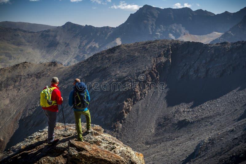 Anonyme Männer, die Ansicht von Bergen bewundern stockfotografie