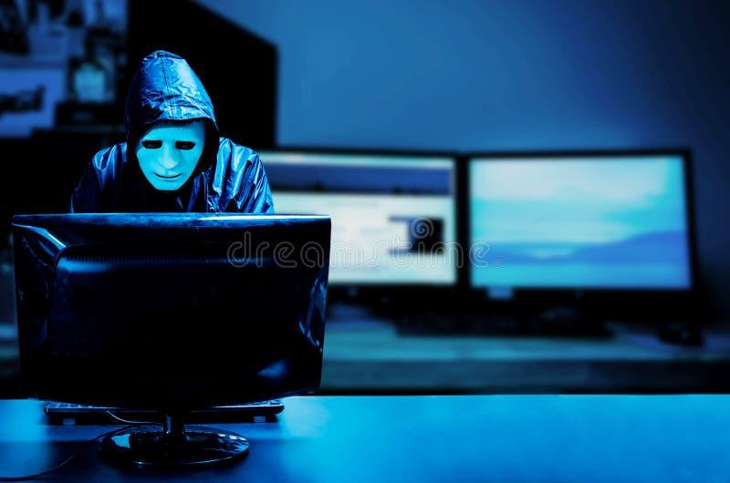 Anonymer Computerhacker in der weißen Maske und im Hoodie Undeutlich gemachte dunkle Gesichtsstellung in der Mitte und Zerhacken  lizenzfreie stockbilder