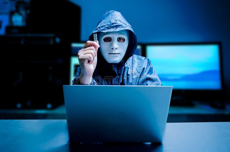 Anonymer Computerhacker in der weißen Maske und im Hoodie Undeutlich gemachtes dunkles Gesicht hält einen grellen Antrieb USBs in lizenzfreies stockbild