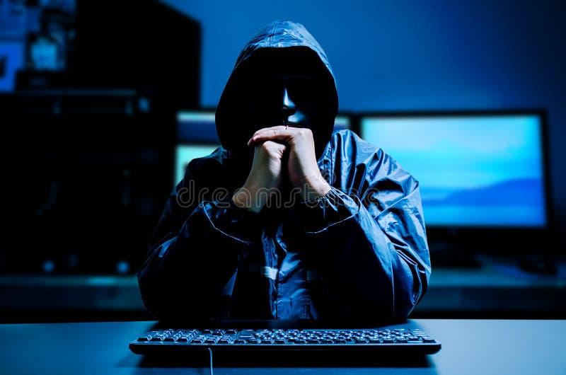 Anonymer Computerhacker in der weißen Maske und im Hoodie Undeutlich gemachtes dunkles Gesicht mit Tastaturcomputer in der Dunkel lizenzfreie stockbilder