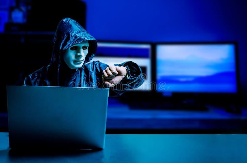 Anonymer Computerhacker in der weißen Maske und im Hoodie Undeutlich gemachtes dunkles Gesicht unter Verwendung der Laptop-Comput lizenzfreie stockbilder