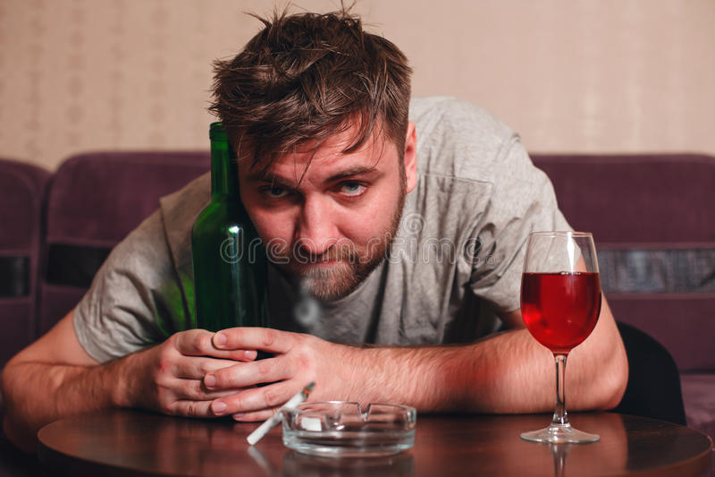 Anonymous alcoholic person in depression. Hard drinking alone royalty free stock image