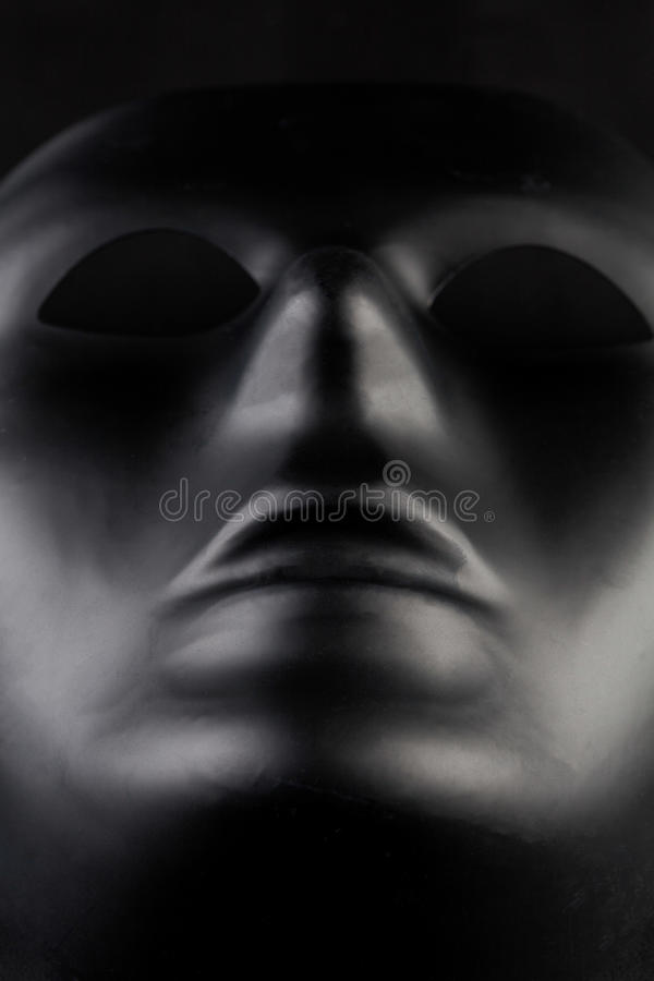 Anonymous black mask protruding from pitch black background - he. Ro shot. Anonymity concept royalty free stock photo