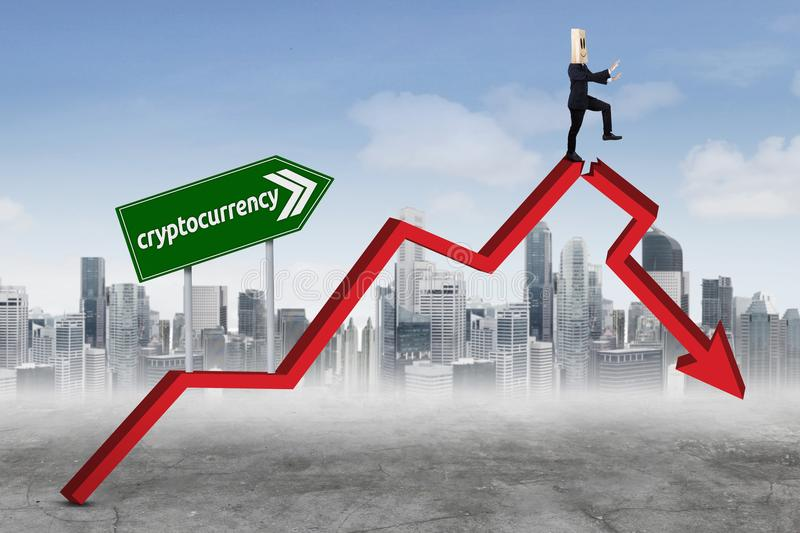 Anonymous businessman with cryptocurrency word. Anonymous businessman finding a way while walking on a declining chart with cryptocurrency word on the signpost stock images