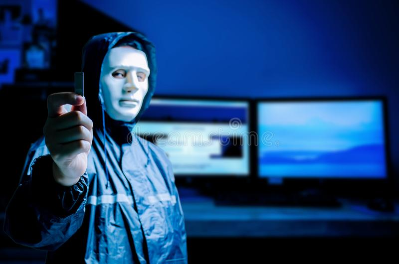 Anonymous computer hacker in white mask and hoodie. Obscured dark face holds a USB flash drive in his hands, Data thief,. Internet attack, darknet and cyber stock photography