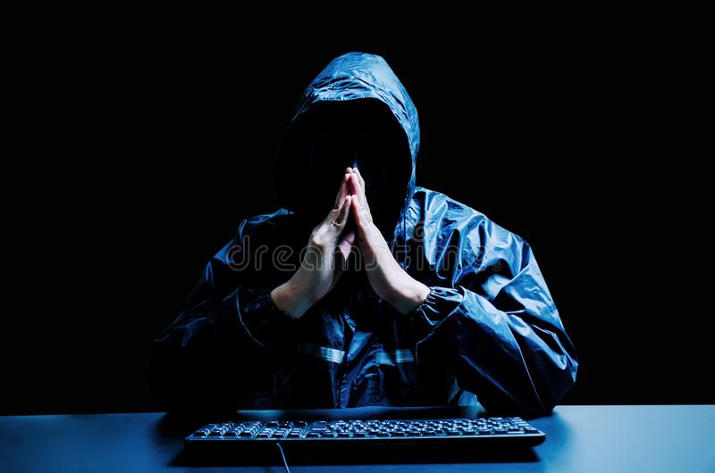 Anonymous computer hacker in white mask and hoodie. Obscured dark face with keyboard computer in the dark. Data thief, internet attack, darknet and cyber royalty free stock images