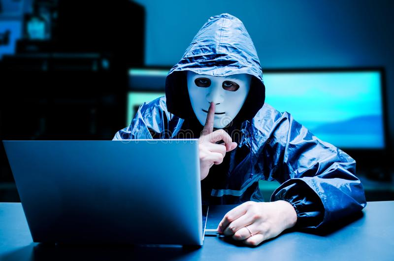 Obscured dark face making silence gesture try to hack and steal information system data from computer with usb thumb drive on dark. Anonymous computer hacker in stock images