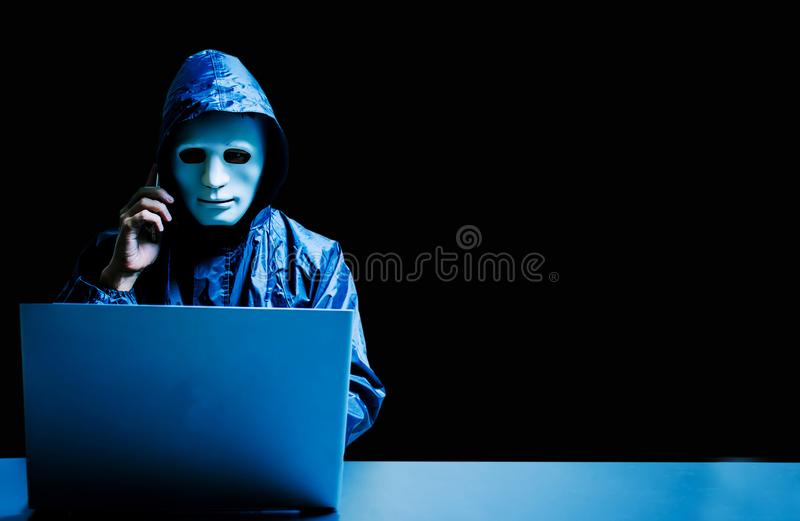 Obscured dark face using laptop computer for cyber attack and calling on cellphone, Data thief, royalty free stock image