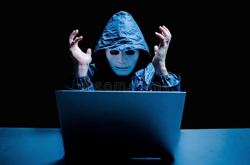 Anonymous computer hacker in white mask and hoodie. Stressful male hacker screaming on a damaged laptop caused by virus,. Data thief, internet attack, darknet royalty free stock images