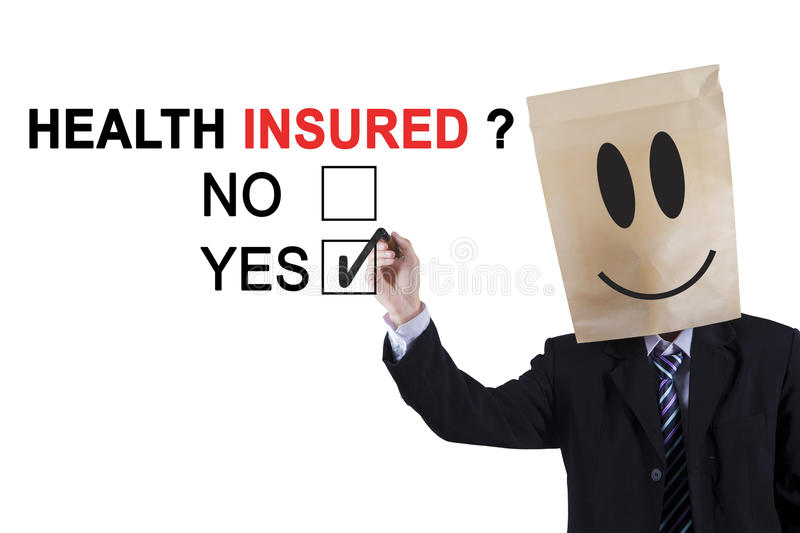 Anonymous entrepreneur agrees about health insured. Male entrepreneur wearing cardboard on his head while using a pen while approving of health insured on the stock photo
