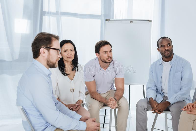anonymous group of multiethnic middle aged people sitting on chairs stock photos
