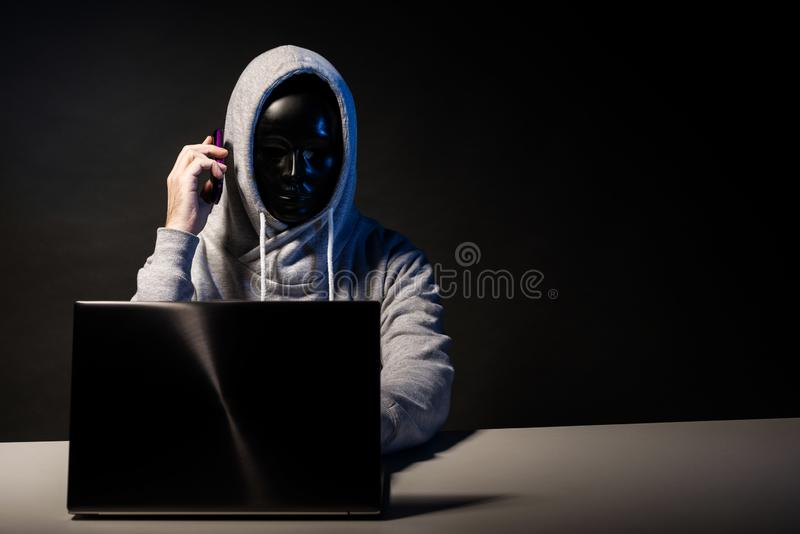 Anonymous hacker in mask programmer uses a laptop and talking on the phone to hack the system in the dark. The concept of cybercrime and hacking database stock images