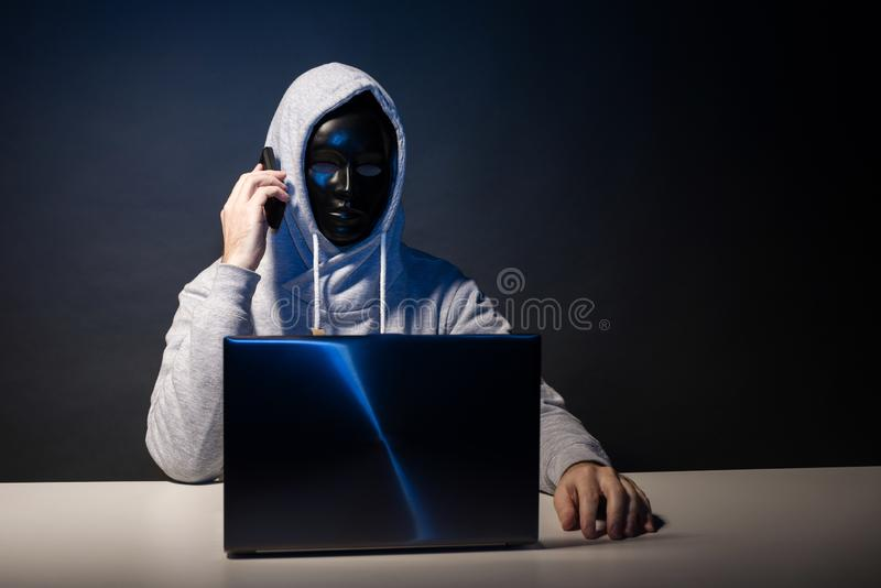 Anonymous hacker in mask programmer uses a laptop and talking on the phone to hack the system in the dark. The concept of cybercrime and hacking database royalty free stock photo