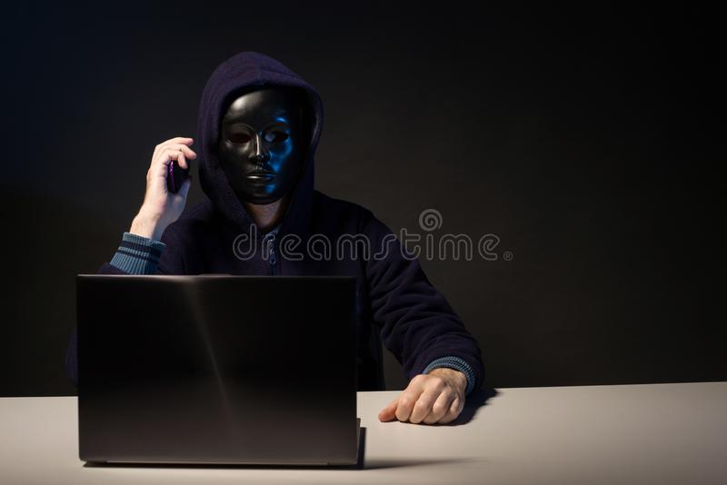 Anonymous hacker in mask programmer uses a laptop and talking on the phone to hack the system in the dark. The concept of cybercrime and hacking database stock image