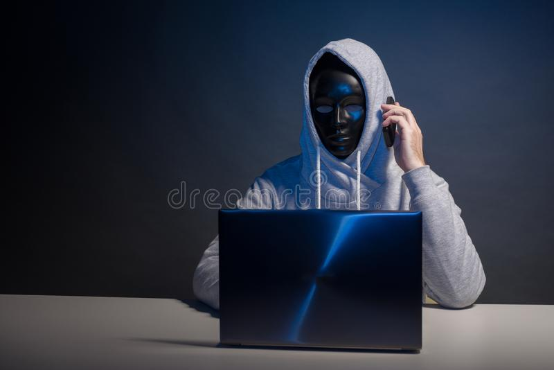 Anonymous hacker in mask programmer uses a laptop and talking on the phone to hack the system in the dark. The concept of cybercrime and hacking database stock photo