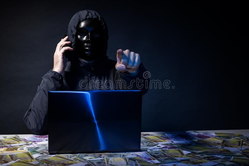 Anonymous hacker in mask programmer uses a laptop and talking on the phone to hack the system in the dark. Anonymous hacker in mask programmer uses a laptop to stock photo