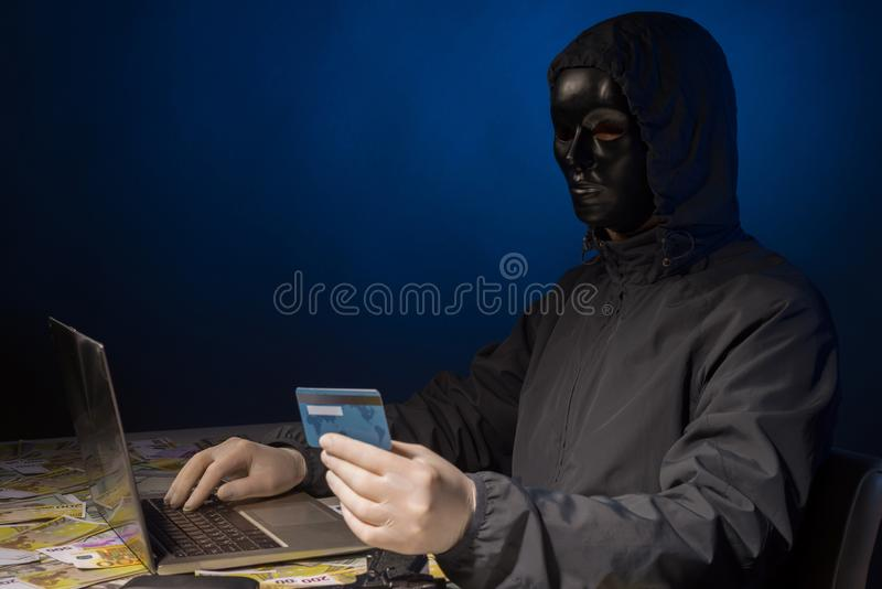 Anonymous hacker in mask programmer uses a laptop to hack the system in the dark. The concept of cybercrime theft of money from bank cards stock images