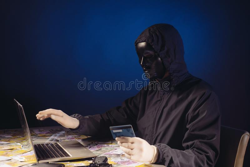 Anonymous hacker in mask programmer uses a laptop to hack the system in the dark. The concept of cybercrime theft of money from bank cards stock photography