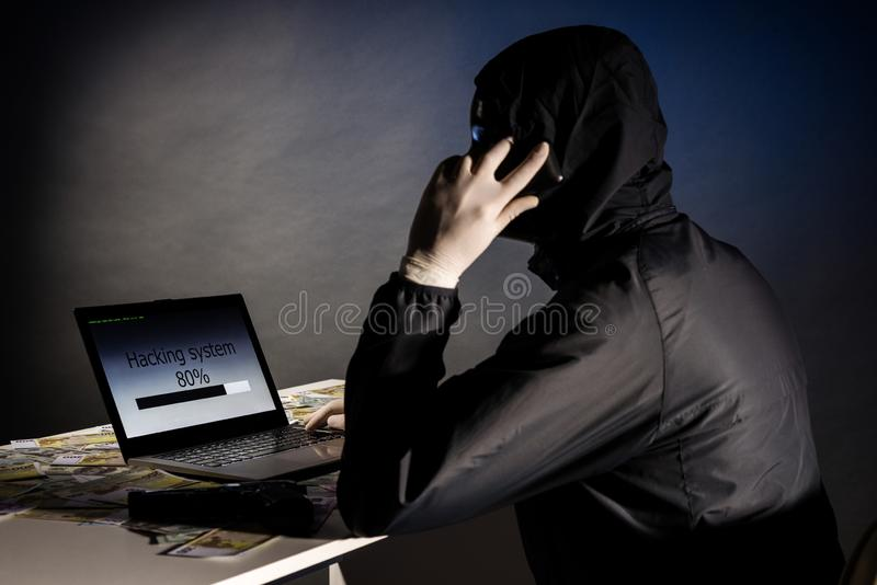 Anonymous hacker in mask sitting sideways uses a laptop and talking on the phone to hack the system in the dark. The concept of. Hacking database. Money is stock photo