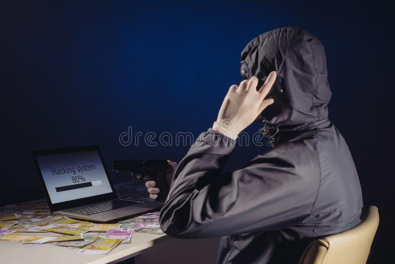 Anonymous hacker programmer uses a laptop holding a gun in his hand to hack the system in the dark. Creation and infection of. Malicious virus. The concept of royalty free stock image
