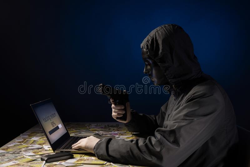 Anonymous hacker programmer uses a laptop holding a gun in his hand to hack the system in the dark. Creation and infection of. Malicious virus. The concept of stock photos