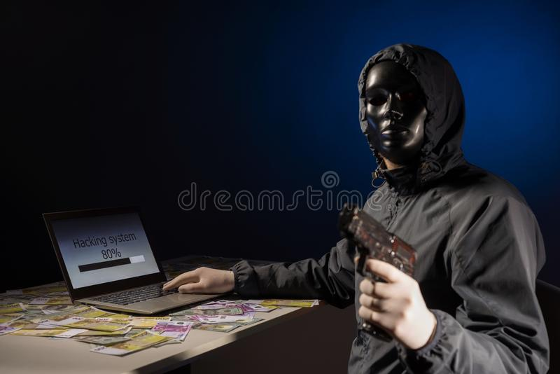 Anonymous hacker programmer uses a laptop holding a gun in his hand to hack the system in the dark. Creation and infection of. Malicious virus. The concept of stock images