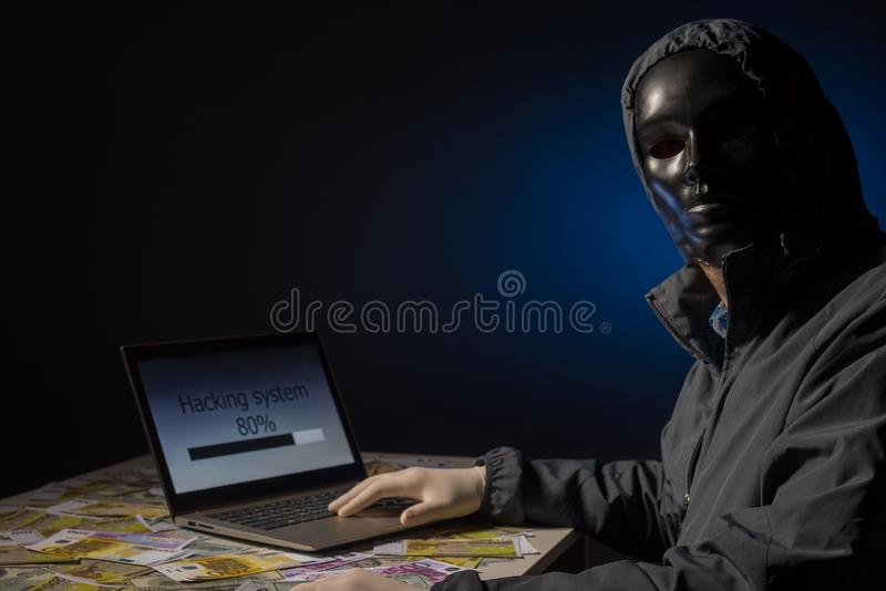 Anonymous hacker programmer uses a laptop to hack the system in the dark. Creation and infection of malicious virus. The concept. Anonymous hacker programmer stock photo