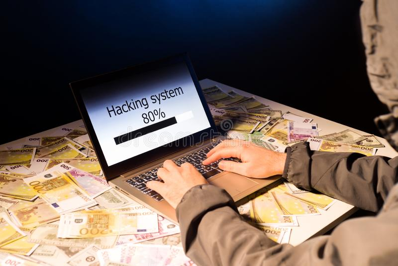 Anonymous hacker programmer uses a laptop to hack the system in the dark. Creation and infection of malicious virus. The concept stock image