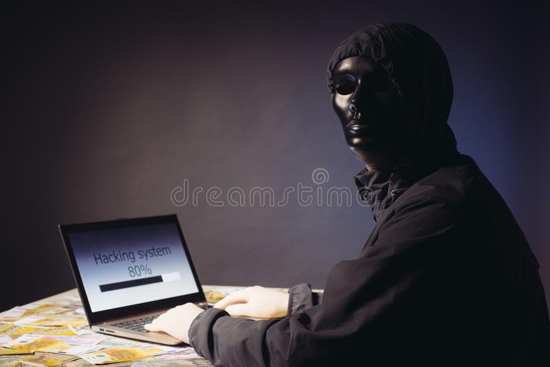 Anonymous hacker programmer uses a laptop to hack the system in the dark. Creation and infection of malicious virus. The concept. Anonymous hacker programmer stock photography