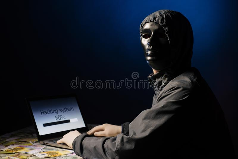 Anonymous hacker programmer uses a laptop to hack the system in the dark. Creation and infection of malicious virus. The concept. Anonymous hacker programmer royalty free stock photography