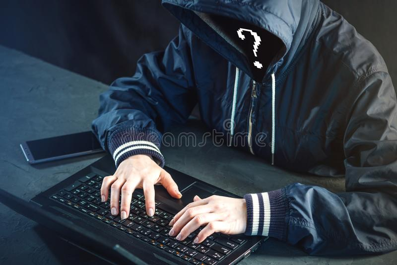 Anonymous hacker programmer uses a laptop to hack the system. St. Ealing personal data. Creation and infection of malicious virus. The concept of cyber crime and royalty free stock photography