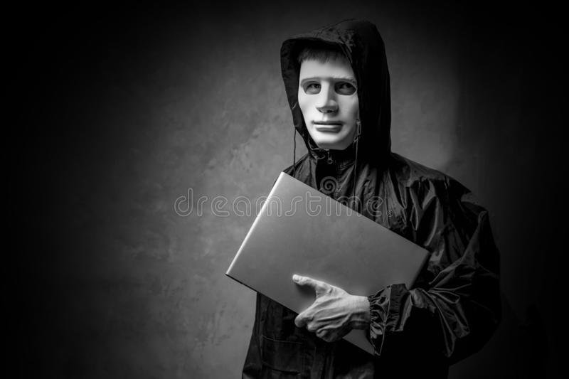 Anonymous hacker in white mask holding a laptop in the dark. Data thief, cyber crime concept. darknet and cyber security concept stock image