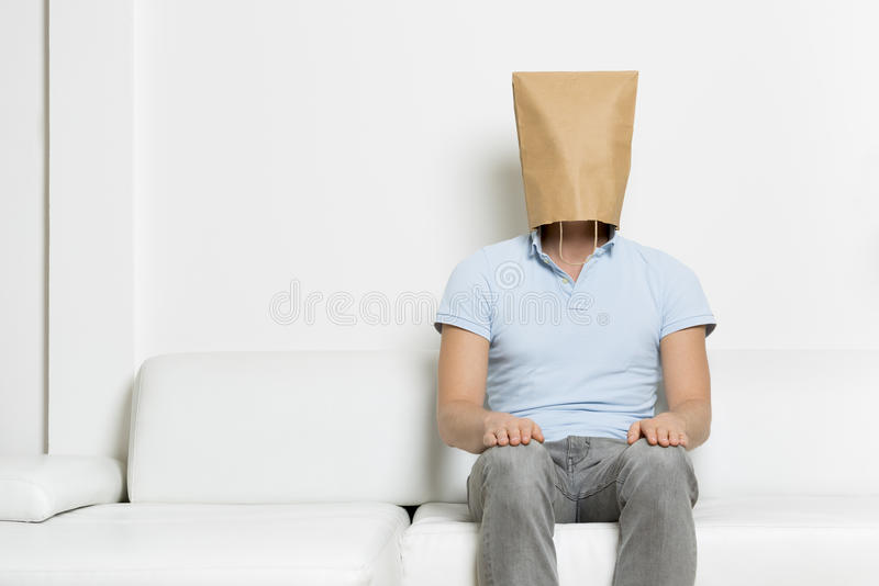 Anonymous inexpressive man with head hidden in a paper bag. Unidentified neutral man with head covered by a brown paper bag sitting on sofa, empty space for stock photography