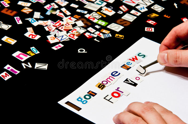 Anonymous informer. Conceptual image of an anonymous informer , person arranging magazine letters on a piece of paper stock photos