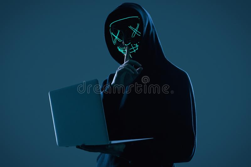 Anonymous Man In A Black Hoodie And Neon Mask Hacking Into A Computer Stock Photo Image Of Night Information 166176358