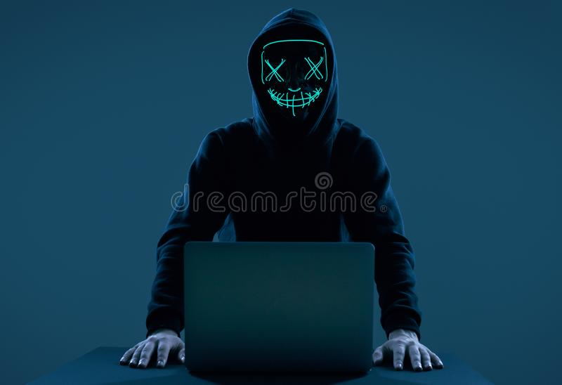Anonymous Man In A Black Hoodie And Neon Mask Hacking Into A Computer Stock Image Image Of Money Breach 166176633