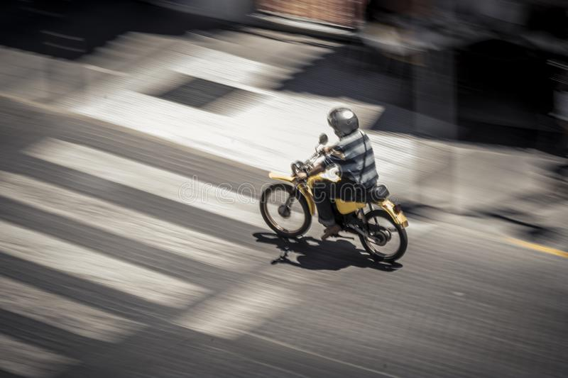 Anonymous man riding motorbike on street royalty free stock photography