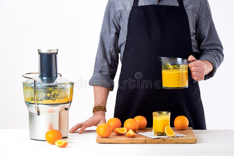 Anonymous man wearing an apron, preparing freshly made orange juice, using modern electric juicer, healthy detox concept. Anonymous man wearing an apron royalty free stock photos