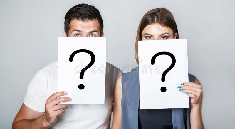 Anonymous, man and woman question. Problems and solutions. Getting answers. Portrait of couple holding paper question stock images