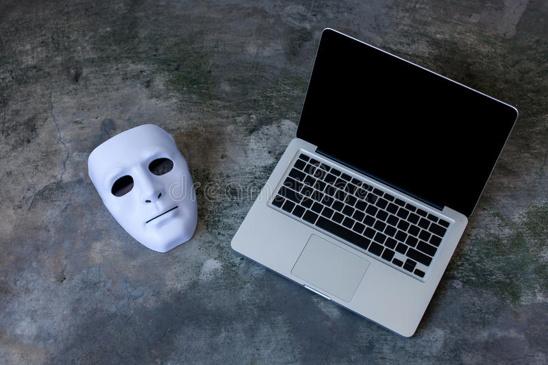 Anonymous mask to hide identity on computer laptop - internet criminal and cyber security threat concept.  stock photo