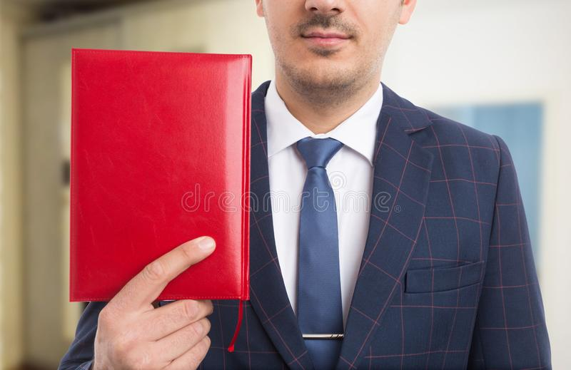 Anonymous pastor holding red bible. Or notebook as believer concept on indoors background stock photography