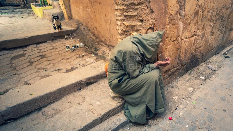 Anonymous poor beggar in the street of Fez, Morocco. stock photos
