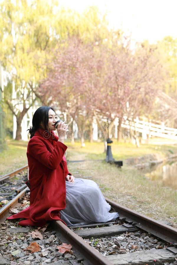 Anonymous woman enjoying takeaway coffee cup on sunny cold fall day royalty free stock photos