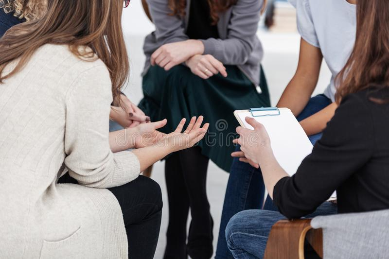 Anonymous women sitting in circle during group meeting. Anonymous women sitting during group meeting stock photos