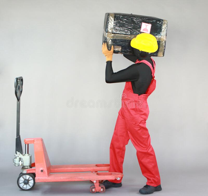 Anonymous worker carrying  heavy package. Profile view. stock photo